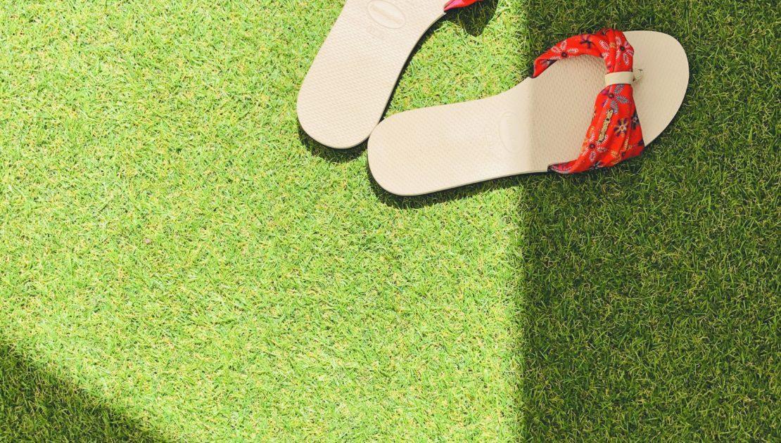 red flip flops on green artificial grass